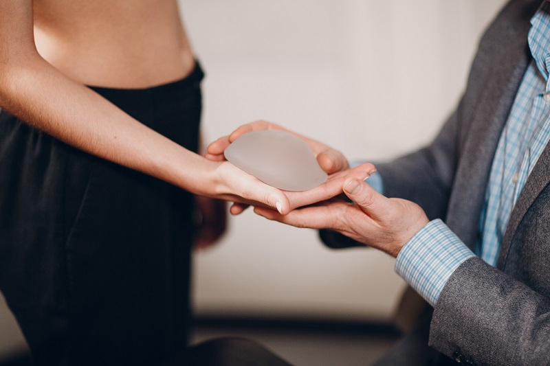 Woman selecting breast implant size in Beverly Hills